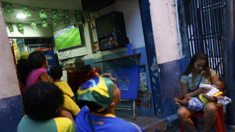 Brazilian soccer fans watch a television from the street during Brazil's game against Cameroon in Rio de Janeiro