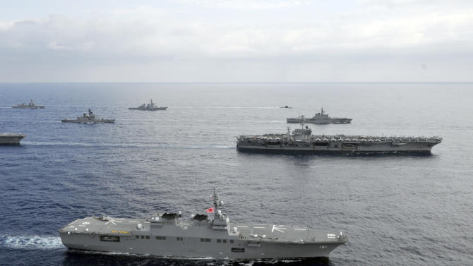 In this photo taken Nov. 16, 2012 and released by U.S. Navy, the USS George Washington aircraft carrier, second row from bottom right, and JS Hyuga, bottom, cruise with other ships from the U.S. Navy and the Japan Maritime Self-Defense Force in East China Sea after the conclusion of Keen Sword, a biennial naval exercise by the two countries to respond to a crisis in the Asia-Pacific region. As U.S. President Barack Obama tours Asia to push his year-old pivot to the Pacific policy, the big question on everybody's mind is how much of a role Washington, with its mighty military and immense diplomatic clout, can play in keeping the Pacific. Japan is Washington's most faithful security partner in the Pacific and it is the most pinched by China's rise. (AP Photo/U.S. Navy, Chief Mass Communication Specialist Jennifer A. Villalovos) EDITORIAL USE ONLY
