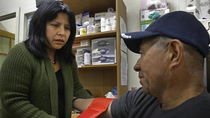 """Laura Lopez, left, checks the blood pressure of Santos Aguilar Wednesday, Jan. 23, 2013, at the Street Level Health Project in Oakland, Calif. In trying to brand California's new health care exchange, state officials had a hard time coming up with a name that signified health insurance, let alone one that would translate well into other languages such as Spanish, Chinese, Tagalog and Vietnamese. The exchange's 5-member board settled on """"Covered California"""" and is currently testing tag lines to see which words resonate best in focus groups. Lopez applauds the exchange for pledging to offer written materials in different languages. But she says the state will have to commit to providing one-on-one interpretive resources because some are illiterate, some don't believe they are qualified for assistance, and some don't know how to advocate for themselves. Many families will also have members with different legal statuses. Covered California estimates there are 5.6 million Californians without health insurance, or 16 percent of the population under age 65. Of that number, 4.6 million people are eligible for coverage under the Affordable Care Act and one million are ineligible due to their immigration status. """"It's another big population that's left behind,"""" Lopez said. (AP Photo/Ben Margot)"""