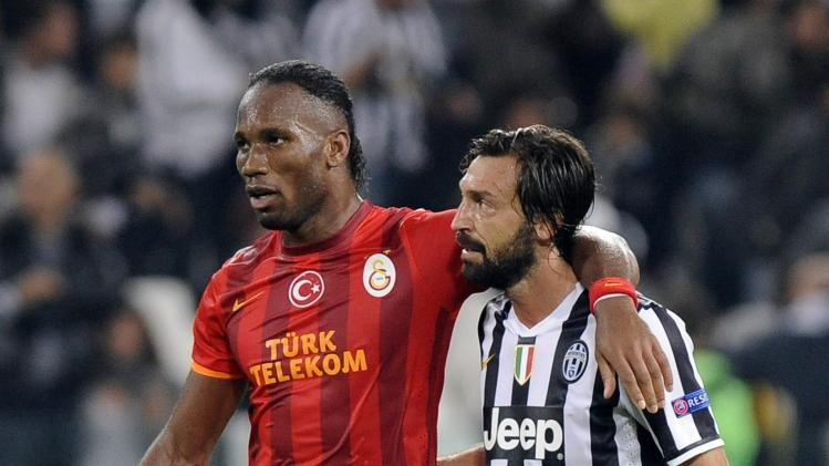 Galatasaray's Drogba and Juventus' Pirlo leave the field after their Champions League soccer match in Turin