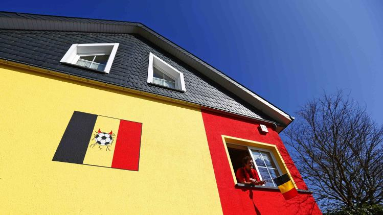 Belgian Wilfried Thelen poses at a window of his house that is painted in the colours of Belgium's national flag in Saint Vith