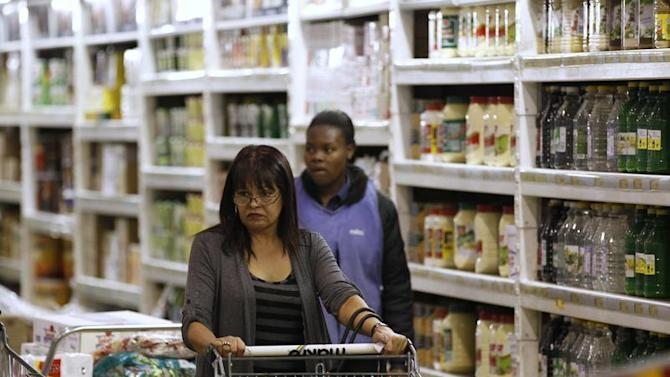 A shopper pushes a trolley of groceries at the Makro branch of South African retailer Massmart in Johannesburg