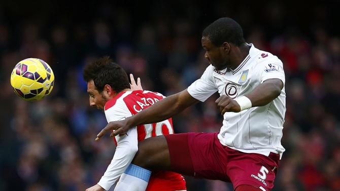 Aston Villa's Okore challenges Arsenal's Cazorla during their English Premier League soccer match in London