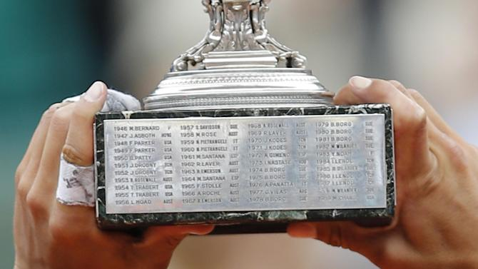 Rafael Nadal of Spain holds the trophy with the inscription of the six titles of Sweden's Bjorn Borg after winning the mens final match against Novak Djokovic of Serbia at the French Open tennis tournament in Roland Garros stadium in Paris, Monday June 11, 2012. Nadal clinched his seventh title in four sets 6-4, 6-3, 2-6, 7-5, passing Sweden's Bjorn Borg as the all-time record-holder for French Open titles. (AP Photo/Christophe Ena)