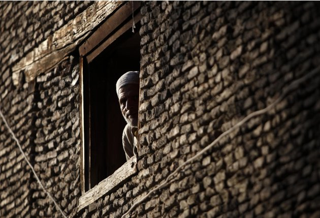 A Kashmir man looks through the window of his house in downtown Srinagar