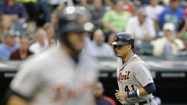 Detroit Tigers' Victor Martinez, right, scores after Alex Avila, left, walked with bases loaded against Cleveland Indians starting pitcher Carlos Carrasco in the second inning of a baseball game, Tuesday, Sept. 2, 2014, in Cleveland. (AP Photo/Tony Dejak)