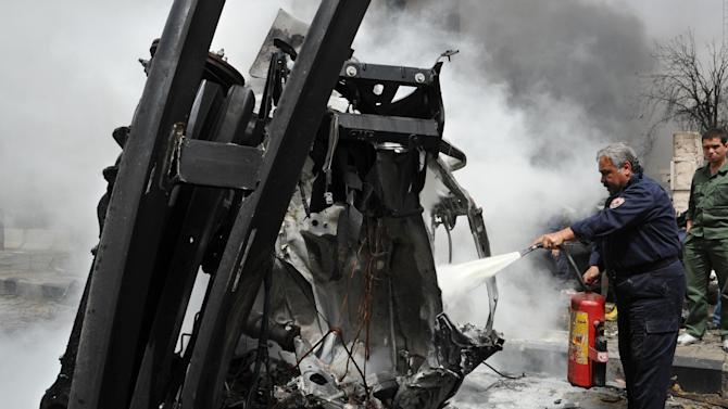 This photo released by the Syrian official news agency SANA, shows a Syrian fire fighter extinguishing a burning car after a huge explosion shook the Sabaa Bahrat Square, one of the capital's biggest roundabouts, in Damascus, Syria, Monday, April. 8, 2013. A car bomb rocked a busy residential and commercial district in central Damascus, killing at least a dozen people with more than fifty injured and causing heavy material damage, a Syrian government official said. (AP Photo/SANA)