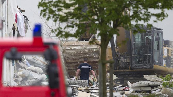 """French firemen attend the scene of a building hit by an explosion that caused the collapse of its inside floors, in Reims, eastern France, Sunday, April 28, 2013.  Five people was killed and ten others injured, according to firefighters, and Reims mayor Adeline Hazan said it awas """"a very powerful explosion"""" and the blast had the earmarks of a possible domestic gas explosion.  (AP Photo/Jacques Brinon)"""