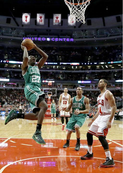 Boston Celtics guard Jordan Crawford (27) scores as teammate Avery Bradley (0) and Chicago Bulls guard D.J. Augustin, right, watch during the second half of an NBA basketball game on Thursday, Jan. 2,