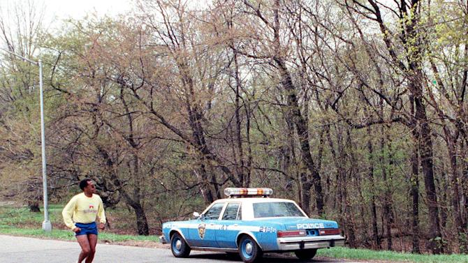 FILE - In this April 21, 1989 file photo, a jogger passes a New York City police vehicle parked near the area where a woman, who came to be known as the Central Park jogger, was raped, beaten and left for dead two nights earlier. Five teenage boys maintained their innocence as they grew up behind bars after being convicted of the rape and beating of the woman. Their convictions were eventually tossed out by a judge when new evidence surfaced linking someone else to the crime. But their legal battle goes on: A $250 million federal lawsuit against police and prosecutors has been pending nearly a decade, with no resolution in sight. (AP Photo/Mario Suriani, File)