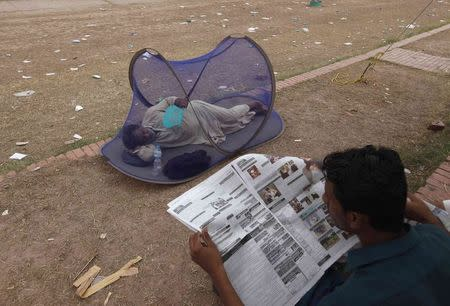 A supporter of Imran Khan, chairman of PTI political party, uses a hand fan as he sleeps in a mosquito tent while another reads newspaper in front of the Parliament building in Islamabad