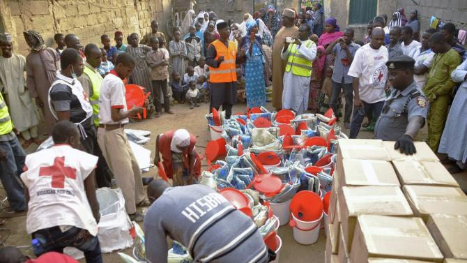 Displaced people gather as the Red Cross in Kano distributes relief materials at a relief camp in Dawaki