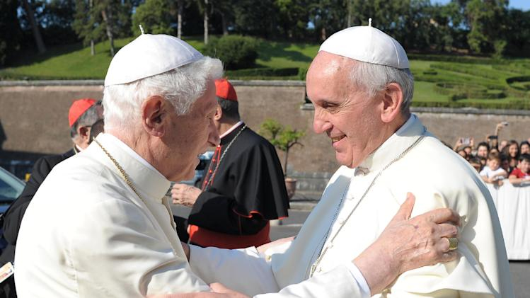 """RETRANSMISSION OF VAT101 TO PROVIDE DIFFERENT CROP- In this photo provided by the Vatican newspaper L'Osservatore Romano, Pope emeritus Benedict XVI, left, is welcomed by Pope Francis during a ceremony for the unveiling of San Michele Arcangelo statue at the Vatican, Friday, July 5, 2013. Francis and Benedict were together Friday morning for the inauguration of the new monument inside the Vatican gardens ó the first time they have been seen together since May 2, when Francis welcomed Benedict back to the Vatican after his initial retirement getaway. Pope Francis issued his first encyclical Friday, a meditation on faith that is unique because it was written with Benedict XVI. Benedict's hand is evident throughout much of the first three chapters of """"The Light of Faith,"""" with his theological style, concerns and reference points clear. (AP Photo/L'Osservatore Romano, ho)"""