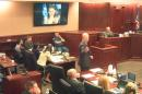 In this image taken from video, Robert Sullivan, second from right, whose granddaughter Veronica Moser-Sullivan, 6, and pictured on the screen at top, was killed by James Holmes, who sits fifth from left in a gray shirt, testifies during the penalty phase of Holmes' trial in Centennial, Colo., Wednesday, Aug. 5, 2015. Prosecutor George Brauchler, center, questions Sullivan. (Colorado Judicial Department via AP, Pool)