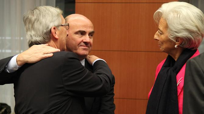 """International Monetary Fund managing director Christine Lagarde, right, looks at Luxembourg's Prime Minister and chairman of the Eurogroup Jean-Claude Juncker, left, and Spanish Economy Minister Luis de Guindos Jurado, during the Eurogroup finance ministers meeting in Brussels, Monday, Nov, 12, 2012. Greece's international lenders have prepared a """"positive"""" report on the country's reform efforts, a crucial step in its efforts to secure the next installment of its bailout loan, the head the of group of finance ministers from the 17 euro countries said Monday. (AP Photo/Yves Logghe)"""