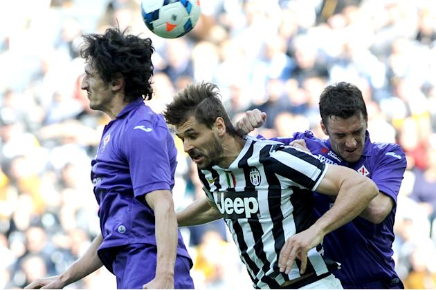 Juventus forward Fernando Llorente, center of Spain, jumps in between Fiorentina defenders Stefan Savic, left, and Gonzalo Rodriguez, during a Serie A soccer match between Juventus and Fiorentina at t