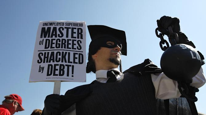 """FILE- In this Oct. 6, 2011, file photo, Gan Golan, of Los Angeles, dressed as the """"Master of Degrees,"""" holds a ball and chain representing his college loan debt, during Occupy DC activities in Washington.  With college enrollment growing, student debt has stretched to a record number of U.S. households — nearly 1 in 5 — with the biggest burdens falling on the young and poor, according to a study based on the Survey of Consumer Finances released Wednesday, Sept. 26, 2012.  (AP Photo/Jacquelyn Martin, File)"""