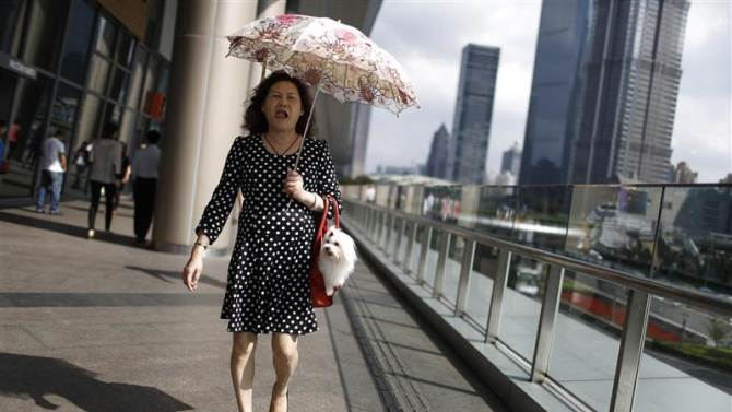 Woman walks with her pet dog at Lujiazui financial district of Pudong in Shanghai