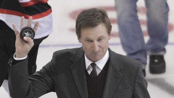 NHL Hall of Fame player Wayne Gretzky waves to the crowd after dropping the official puck before the start of Game 3 of the Stanley Cup Finals between the Los Angeles Kings and New Jersey Devils, Monday, June 4, 2012, in Los Angeles.  (AP Photo/Jae C. Hong)