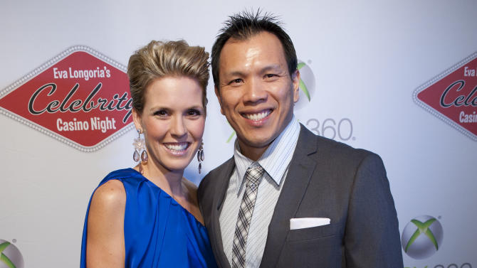 Former Dallas Cowboys linebacker Dat Nguyen, right, stands with his wife, Becky Nguyen, on the red carpet at Eva Longoria's Celebrity Casino Night benefitting Eva's Heroes and presented by Xbox 360, on Saturday, Oct. 6, 2012 in San Antonio, Texas. (Photo by Darren Abate/Invision for Xbox 360/AP Images)