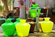 A woman collects drinking water in plastic pots from a community tap in Bangalore in March 2012. A report has found that water demand in the world's two most populous countries, India and China, will exceed supplies in less than two decades