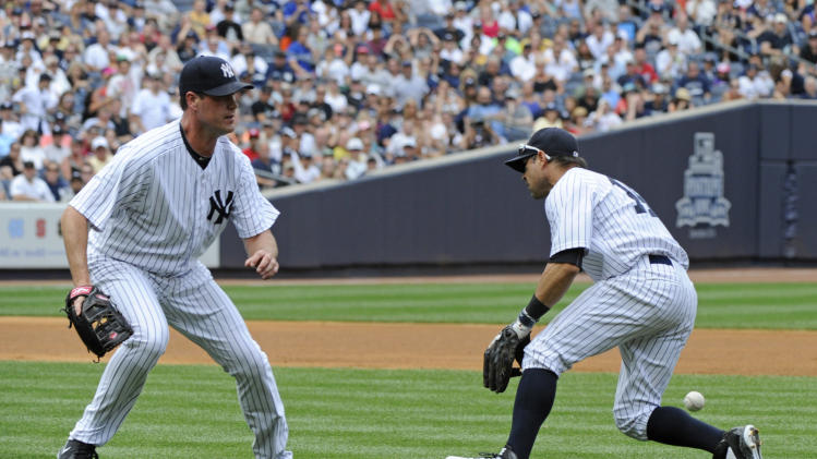 New York Yankees second baseman Brian Roberts is unable to catch a RBI-single in the infield by Toronto Blue Jays' Dan Johnson as Yankees pitcher Matt Thornton, left, looks on during the seventh inning of a baseball game Saturday, July 26, 2014, at Yankee Stadium in New York. (AP Photo/Bill Kostroun)