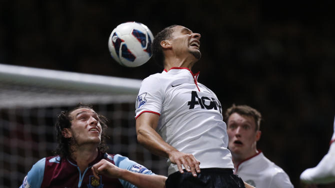 Manchester United's Rio Ferdinand, center, is watched by Phil Jones, right, as he gets to the ball ahead of West Ham's Andy Carroll, left, during the English Premier League soccer match between West Ham and Manchester United at Upton Park stadium in London, Wednesday, April 17, 2013.  (AP Photo/Matt Dunham)
