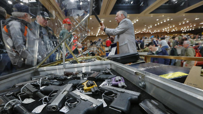 FILE - In this Saturday, Jan. 26, 2013 file photo, handguns appear on display at the table of David Petronis of Mechanicville, N.Y., standing with rifle, who owns a gun store, during the heavily attended annual New York State Arms Collectors Association Albany Gun Show at the Empire State Plaza Convention Center, in Albany, N.Y. Key measures of New York's tough new gun law are set to kick in, with owners of guns now reclassified as assault weapons required to register the firearms and new limits on the number of bullets allowed in magazines. As the new provision takes effect Monday, April 15, 2013, New York's affiliate of the National Rifle Association said it plans to head to court to seek an immediate halt to the magazine limit. (AP Photo/Philip Kamrass, File)