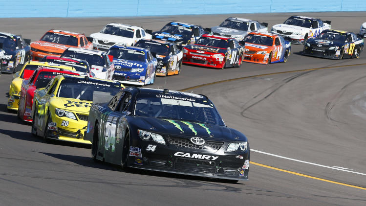 Kyle Busch leads a line cars out of Turn 4 during the NASCAR Nationwide Series auto race Saturday, March 2, 2013, in Avondale, Ariz. (AP Photo/Ross D. Franklin)