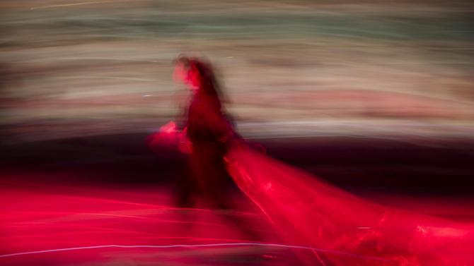 In this photo made with a long exposure, a production assistant removes the protective plastic tarp from the runway before the Vivienne Tam Fall 2013 fashion show during Fashion Week, Sunday, Feb. 10, 2013, in New York. (AP Photo/John Minchillo)