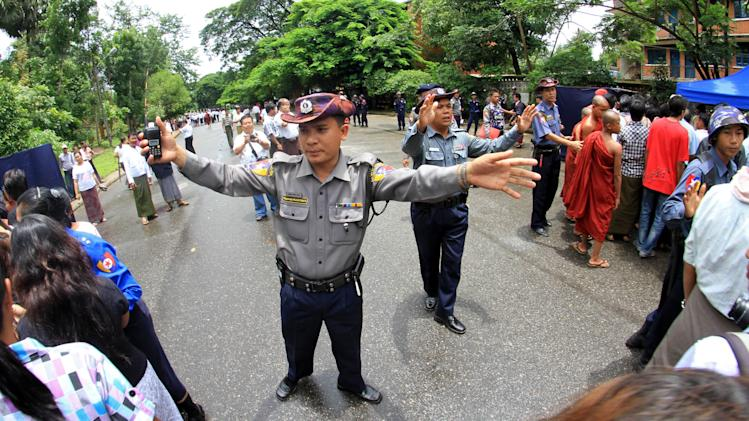 Myanmar riot policemen control people gathered on a road leading to the Martyrs' Mausoleum to pay tribute to the nation's independence heroes during Martyrs' Day ceremonies Tuesday, July 19, 2011, in Yangon, Myanmar. (AP Photo/Khin Maung Win)