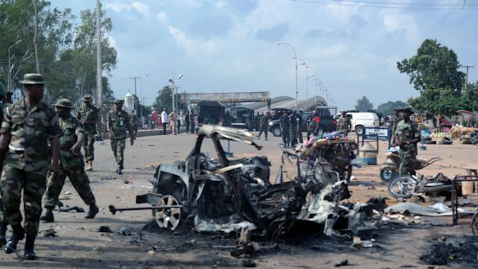 Military officers walk past the remains of a car after an explosion on July 23, 2014 in Kaduna, Nigeria