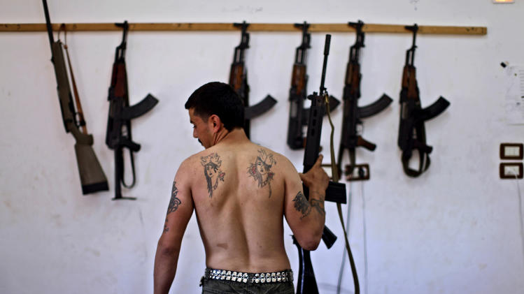 FILE - In this Sunday, Aug. 26, 2012 file photo, Syrian rebel fighter Tawfiq Hassan, 23, a former butcher, poses for a picture, after returning  from fighting against Syrian army forces in Aleppo, at a rebel headquarters in Marea on the outskirts of Aleppo city, Syria. America's Arab allies have dramatically stepped up weapon supplies to Syrian rebels in preparation for a push on the capital Damascus, the main stronghold of President Bashar Assad, officials and Western military experts say, with one official saying airlifts to neighboring Jordan and Turkey have doubled the past month. The U.S. and other Western governments are involved to channel the flow toward more secular fighters, they say. The influx appears to be boosting a rebel drive to seize supply routes from the border with Jordan to Damascus.  (AP Photo/Muhammed Muheisen, File)