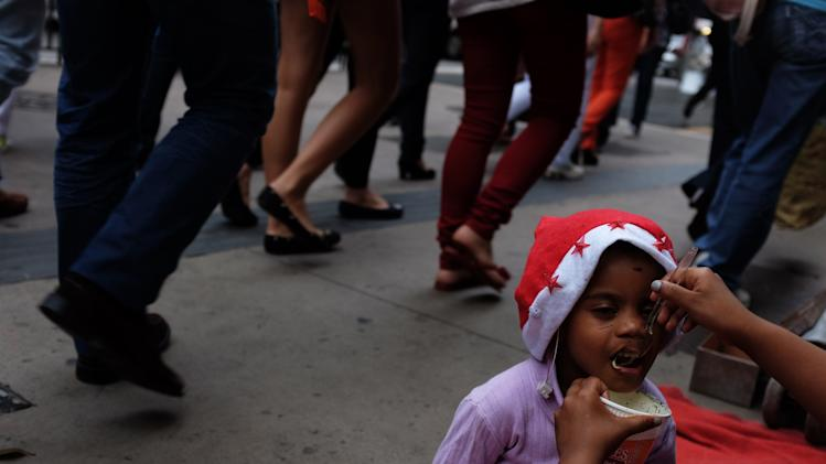 The daughter of a homeless person wears a Christmas hat as she eats on the street in the financial centre of Sao Paulo's Avenida Paulista