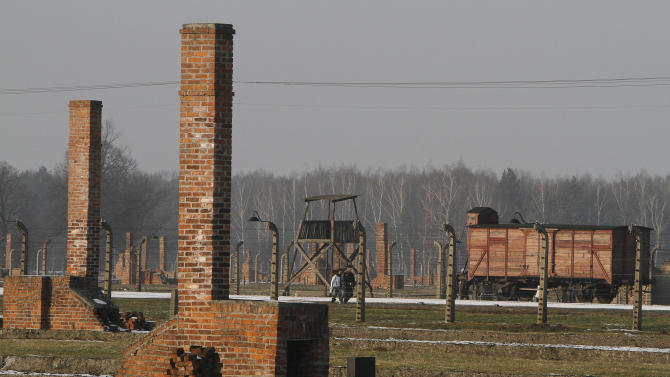 "This image taken Jan 28. 2011 shows people walking  through the Nazi death camp Auschwitz-Birkenau in Oswiecim, Poland.  The red brick barracks that housed starving inmates are sinking into ruin. Time has warped victims' leather shoes into strange shapes. Hair sheared to make cloth is slowly turning to dust. Officials  launched a global campaign to raise euro120 million ($165 million) to create a ""perpetual fund"" whose interest can be drawn on indefinitely to repair barracks, watchtowers, crematoria and other structures at the Auschwitz-Birkenau state museum and memorial in southern Poland. (AP Photo/Czarek Sokolowski)"