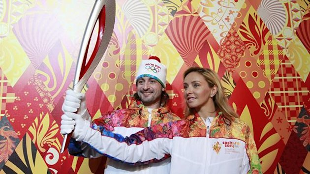 Russian ice dancers Tatyana Navka (R) and Ilya Averbukh hold the Olympic torch for the Sochi 2014 Winter Olympics during a presentation ceremony in Moscow (Reuters)