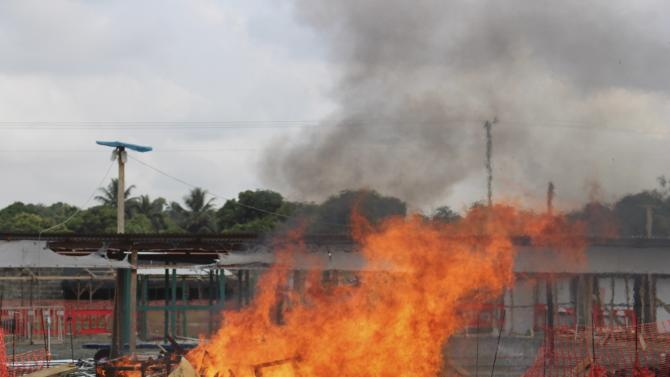 A portion of a MSF Ebola treatment unit burns as the MSF begins decommissioning the facility in Monrovia, Liberia