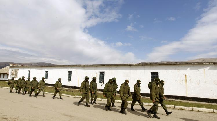 Armed men, believed to be Russian servicemen, walk outside a Ukrainian military base in Perevalnoye
