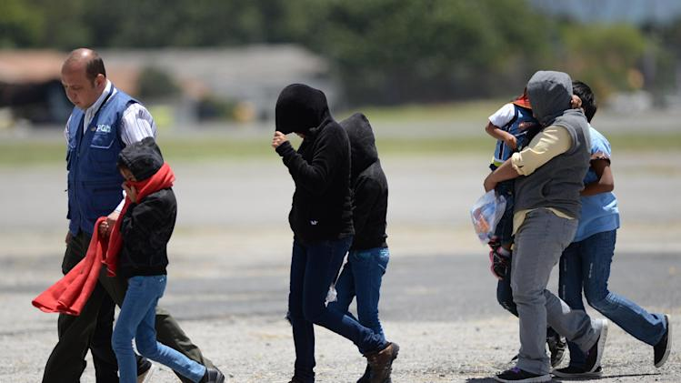 A group of children and seven mothers arrive in Guatemala after being deported from the United States on July 22, 2014