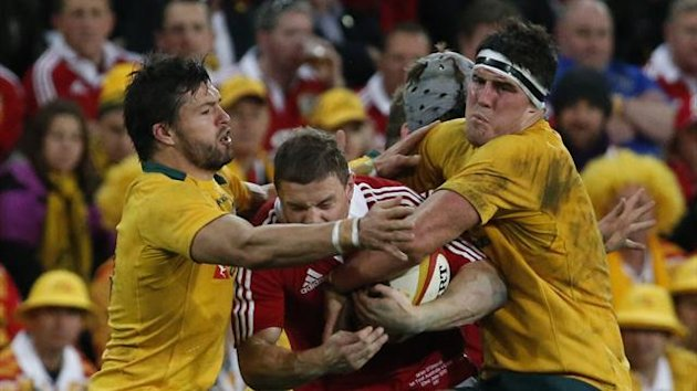 Brian O'Driscoll (C) is tackled by Australia's Adam Ashley-Cooper (L) and James Horwill (Reuters)