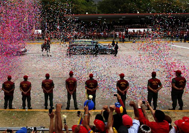 Confetti falls around the hearse carrying the coffin that contains the remains of Venezuela's late President Hugo Chavez, in a funeral procession, in Caracas, Venezuela, Friday, March 15, 2013. Chavez