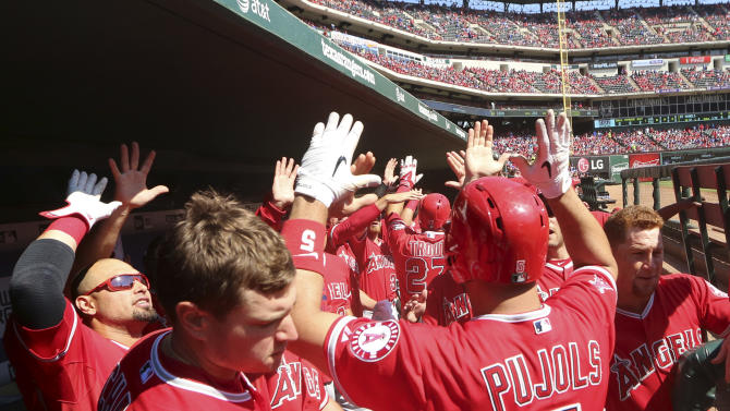 Los Angeles Angels Albert Pujols (5) celebrates his two run homer with teammates in the dugout during the first inning of a baseball game against the Texas Rangers in Arlington, Texas, Sunday, Oct. 4, 2015. AP Photo/LM Otero)