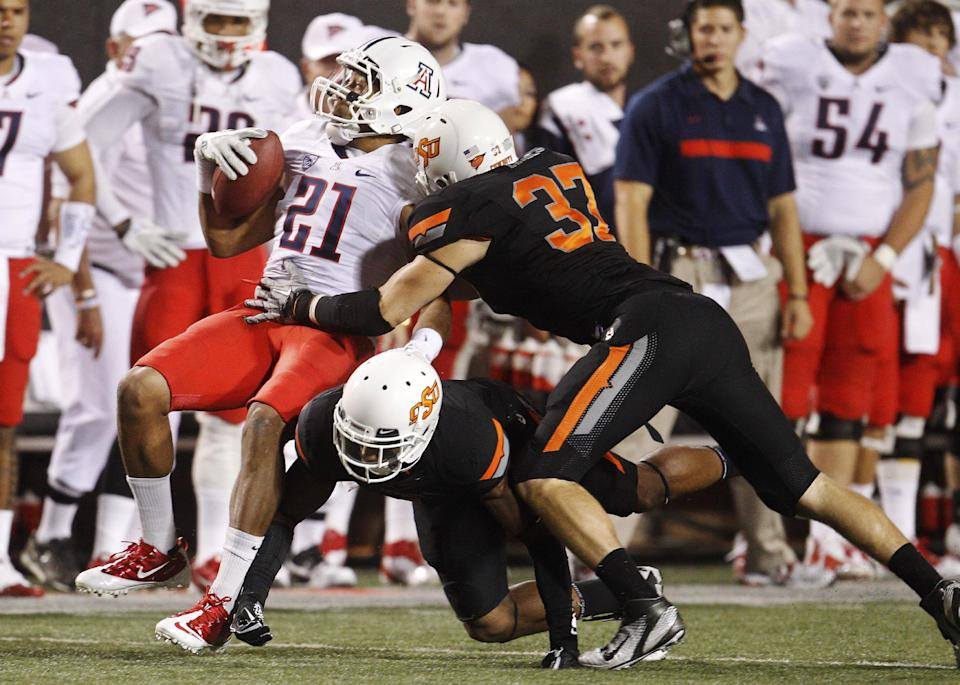Oklahoma State linebacker Alex Elkins, right, reaches in to tackle Arizona wide receiver Gino Crump, left, in the fourth quarter of an NCAA college football game in Stillwater, Okla., Thursday, Sept. 8, 2011. Oklahoma State won 37-14. (AP Photo/Sue Ogrocki)