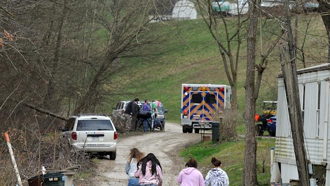 """Friends and neighbors walk up and down the gravel road leading to Shain Gandee's home in Sissonville, W.Va., Monday afternoon, April 1, 2013. Gandee, star of the MTV show """"Buckwild""""; his uncle, David Gandee; and Donald Robert Myers were found dead in the family's Ford Bronco Monday morning. (AP Photo/The Charleston Gazette, Chip Ellis)"""