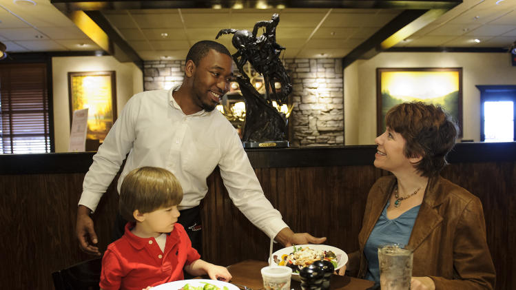 """IMAGE DISTRIBUTED FOR LONGHORN STEAKHOUSE - Edarius, an Atlanta-area LongHorn Steakhouse team member, serves Michelle and her son David on International Children's Book Day on Tuesday, Apr. 2, 2013. Today only, LongHorn is offering a """"Give a Book, Get a Free Kid's Meal"""" promotion, benefiting local Boys & Girls Clubs across the country. With each children's book donation, guests will receive a free kid's meal with the purchase of one adult entrée. (Paul Abell / AP Images for LongHorn Steakhouse)"""