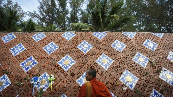 A Buddhist monk looks on at a wave-shaped tsunami monument for the victims of the 2004 tsunami in Ban Nam Khem