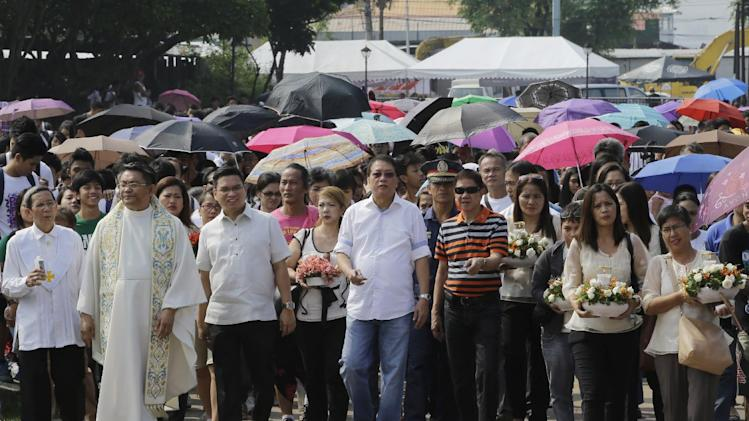 Catholic priest father Sanny De Claro, second from left, leads students and residents in offering flowers and lighting candles at the site at the Quirino grandstand in Manila, Philippines to commemorate the bus hostage incident four years ago Saturday, Aug. 23, 2014. Four years ago, a disgruntled police officer took hostage a tourist bus carrying Hong Kong tourists and the police rescue operation saw the death of eight Hong Kong tourists. The incident has soured relations between the Philippines and Hong Kong. (AP Photo/Bullit Marquez)