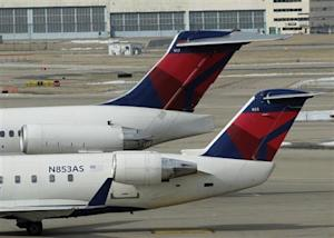 Two delta Airlines jets sit at their gates at the Lambert - St. Louis International Airport