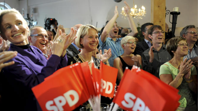 Supporters of the governor of  Mecklenburg-Western Pomerania Erwin Sellering react during an election party of the Social Democrats Party, SPD, in Schwerin, northern Germany, Sunday, Sept. 4, 2011. The ARD television exit poll put the center-left Social Democrats ahead in Sunday's election with 37 percent support _ an improvement over five years ago _ but showed German Chancellor Angela Merkel's conservative Christian Democrats sliding to 24 percent. (AP Photo/dapd, David Hecker)