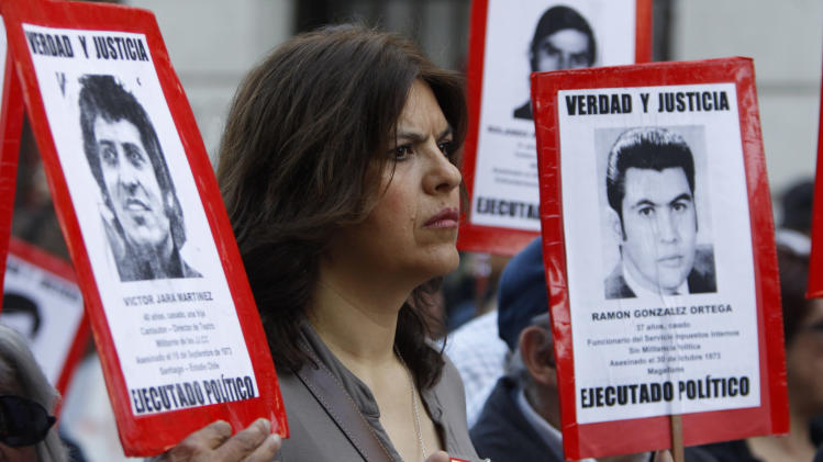 "A demonstrator gestures as she holds a portrait of a victim during a march marking the 38th anniversary of Augusto Pinochet's military coup in Santiago, Chile, Sunday, Sept. 11, 2011. Pinochet assumed power on Sept. 11, 1973, in a coup supported by the United States that toppled the elected government of Salvador Allende. The sign she holds reads in Spanish: "" True and justice, Ramon Gonzalez Ortega, Politically Executed.""(AP Photo/Aliosha Marquez)"